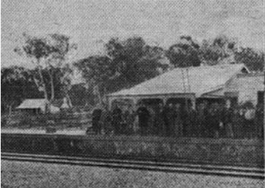 Photo. of Glenrowan railway station, showing Mrs. Jones' Glenrowan Inn in the background. This picture was taken while the hotel, containing Dan Kelly, Steve hart, and Martin Cherry, was still under siege by 50 police armed with Martini-Henry rifles, and about two hours before the hotel was fired, and burnt down. The fifth figure from the left is Dean Gibney.